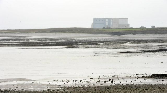 Ebbe an einem flachen Meeresufer, in der Ferne die Kraftwerkgebäude.