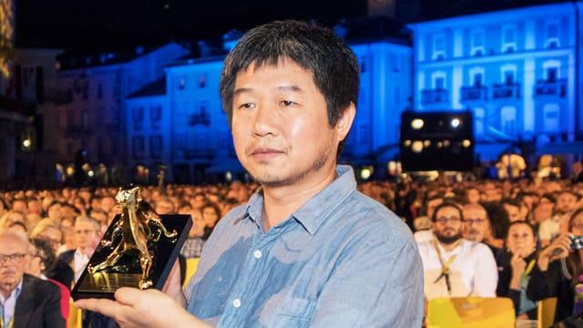 Ein Mann hält eine goldene Leoparden-Statue. im Hintergrund Publikum auf der Piazza Grande in locarno.