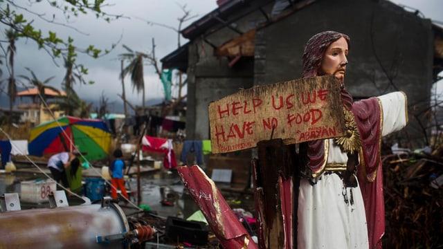 Eine Jesusstatue mit einem Schild, worauf eine Bitte um Hilfe steht.