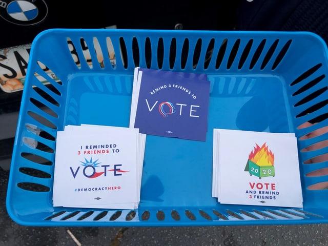 Ein blauer Plastikkorb mit Klebern demokratischer Wahl-Aktivisten.