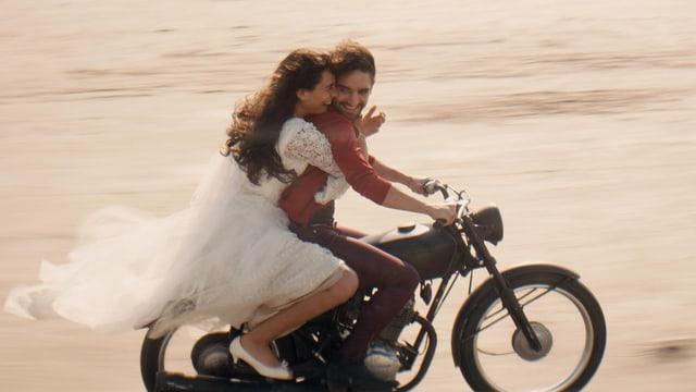 Frau im Brautkleid mit Mann auf Motorrad