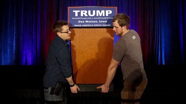 Zwei Arbeiter schleppen ein Rednerpult mit einem Trump-Schild daran weg.