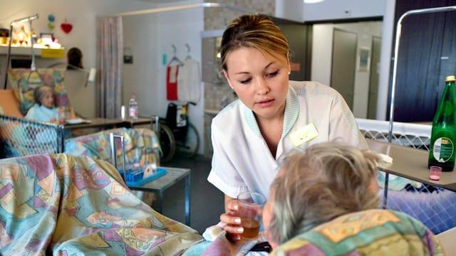 Pflegerin betreut eine alte Frau.