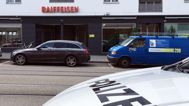 Blick auf die Raiffeisenbank von der Strasse. Im Vordergrund ein Schriftzug eines Polizeifahrzeugs