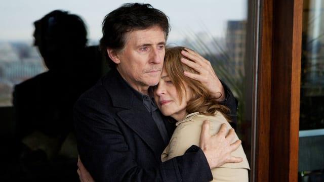 Bernie Reid halt Charlotte Rampling im Arm. Beide stehen vor einer Glasscheibe, in der sich verschwommen der Anblick einer Stadt spiegelt.
