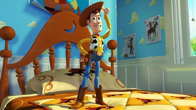 Spielzeugfigur Woody steht auf einem Bett.
