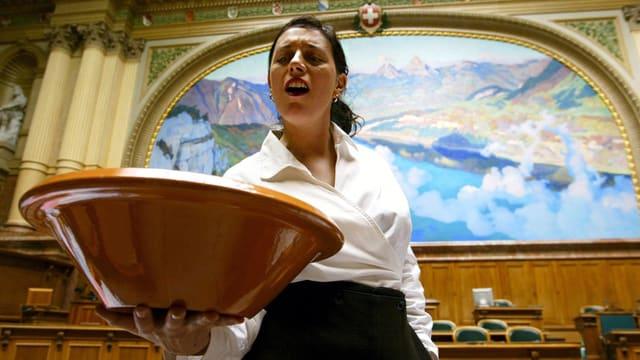 Eine Frau steht im Nationalratssaal und hält eine grosse braune Schüssel in der Hand.