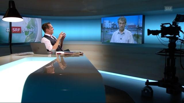 Moderator Florian Inhauser spricht im Studio mit dem aus Qamishli zugeschalteten Taha Khalil, den man auf dem Monitor sieht