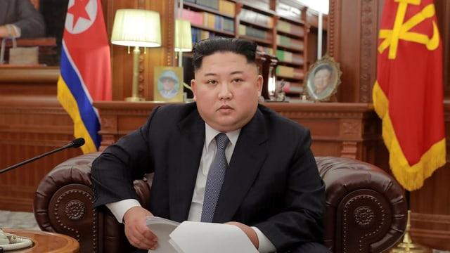 Kim in einem Sofa sitzend und die Rede in den Händen haltend.