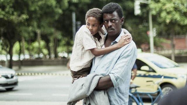 Ein Mann trägt ein Mädchen auf dem Arm über eine Strasse.