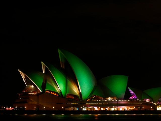 Die Oper von Sydney bei Nacht. Sie ist grün beleuchtet.