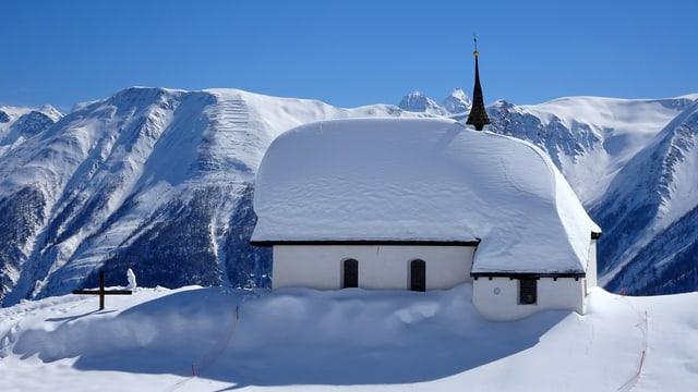 Tief verschneite Kirhce auf der Bettmeralp vor stahlblauem Himmel.