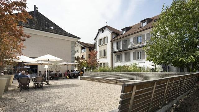 Blick auf einen Dorfplatz mit Tischen und Stühlen und historischen Gebäuden im Hintergrund.