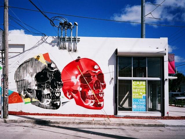 Ein schwarz-weisser und ein roter Totenkopf auf einer weissen Hauswand.