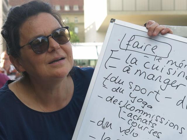 Kursleiterin Marie Lebouteiller mit einem Whiteboard in den Händen.