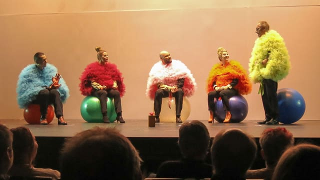 Fünf Personen sitzen auf Gymnastikbällen und sprechen miteinander.