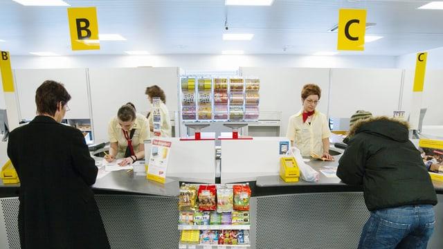 Postfiliale mit Mitarbeitenden und Kunden.