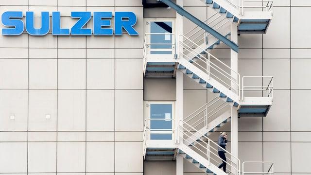 Fassade mit dem Schriftzug von Sulzer und einer Feuertreppe, auf der eine Frau abwärts läuft.