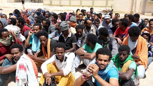 Eine Gruppe afrikanische Männer sitzen in einer Gruppe zusasmmen.