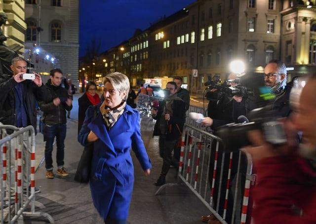 Frau, umringt von Medienleuten.