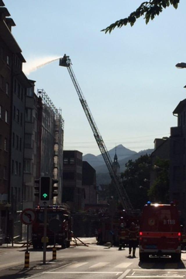 Ein Feuerwehrkran löscht Feuer an einem hohen Gebäude.