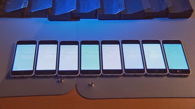 Acht Handy nebeneinander mit leuchtendem Display.