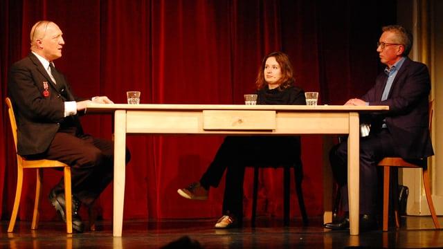 Drei Menschen sitzen am Tisch