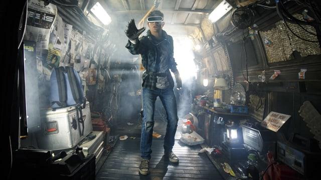 Ein junger Mann mit VR-Brille steht in einem zugemüllten Lieferwagen und streckt die Hand aus.