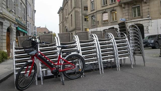 Ein Fahrrad steht vor einem Stapel Stühle auf der Strasse.