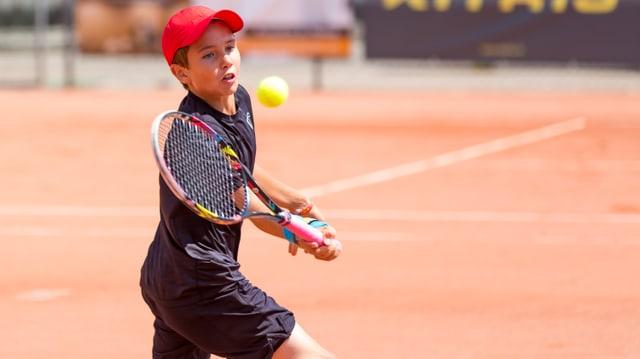 Knabe am Tennisspielen