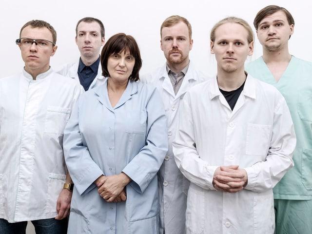 Vier Männer und eine Frau in matten Kitteln blicken ernst in die Kamera.
