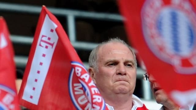 Der Präsident des FC Bayern, Uli Hoeness, inmitten von FC Bayern Flaggen.