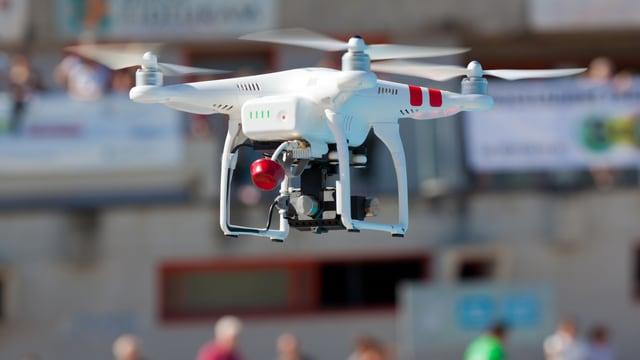 Eine Drohne fliegt über Menschen hinweg