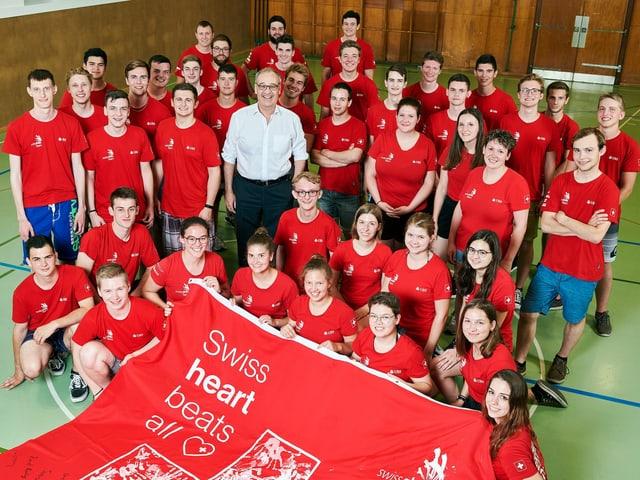 Bundesrat Guy Parmelin steht inmitten von rund 40 jungen Berufsleuten in rotem T-Shirt.