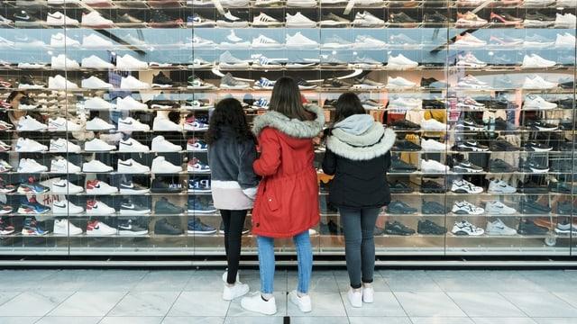 Drei Teenager stehen vor einem Schaufenster voller Sneakers