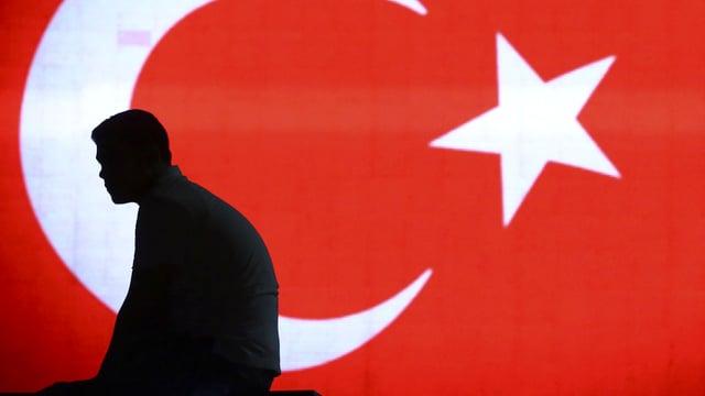 Mann sitzt vor türkischer Flagge.