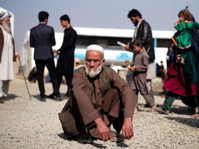 Ein alter Mann kniend, dahinter weitere Vertriebene