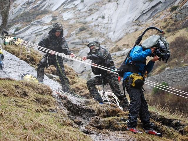 Bergretter der Schweizer Armee richten eine Seilrettung ein. Der Kameramann begleitet sie dabei.