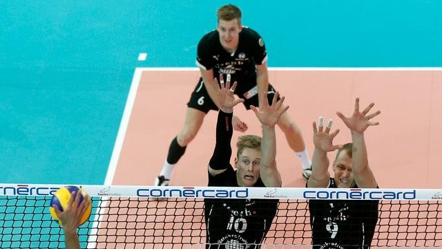 2 Männer springen hoch und heben die Hände, während eine Hand versucht den Ball über das Netz zu spielen.