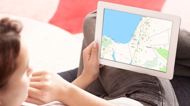 Eine Frau schaut sich eine Karte auf einem Tablet an.