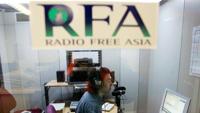 Eine Logo von Radio Free Asia unscharf im Vordergrund, hinten ein Mann am Mikrofon.