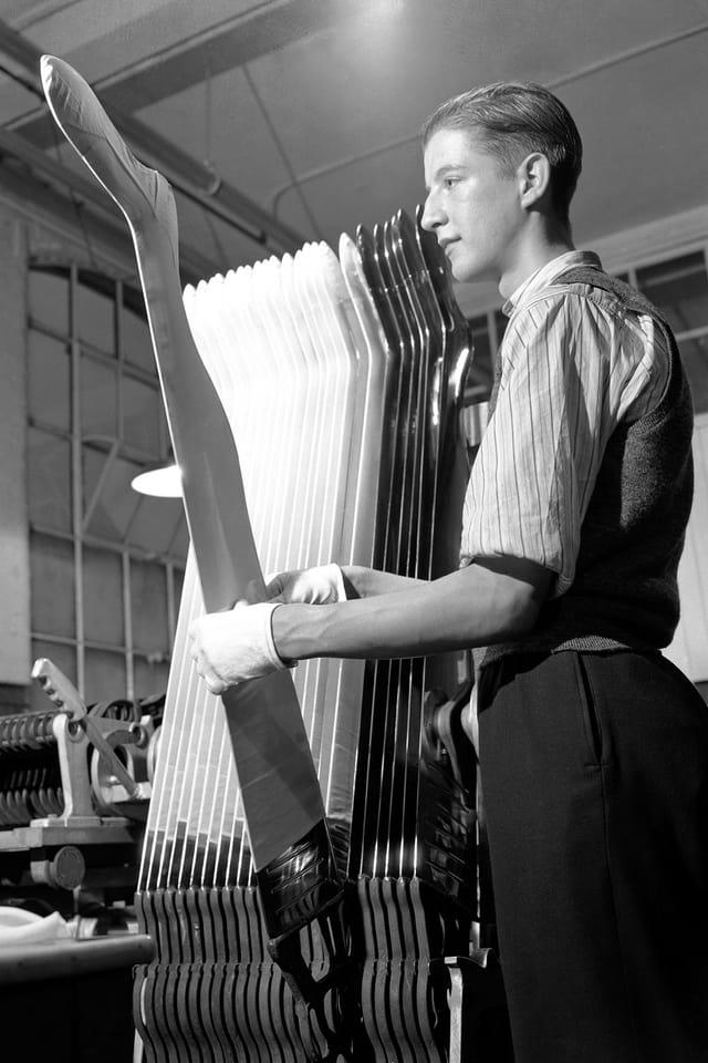Ein Mann spannt Strumpfhosen auf.
