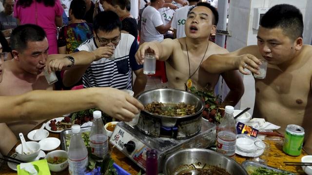 Vier Männer, stossen an und essen ein Hundefleisch Gericht.