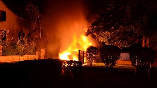 Flammen schiessen in der Nacht in die Luft, daneben Wohnhäuser.