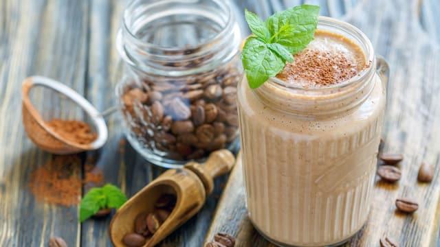 Mokka-Joghurt im Glas, verziert mit Kaffeebohnen und Blättern.