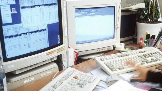 Zwei Bildschirme mit Kursdaten und zwei Tastaturen mit einer Hand an einem Handelsarbeitsplatz einer Bank