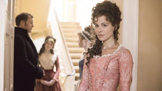 Eine Frau mit Hochsteckfrisur und im pompösem, rosaroten Kleid lehnt am Türrahmen.
