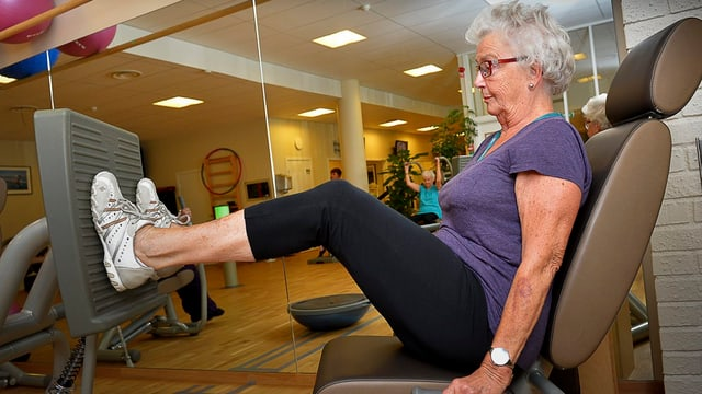 Zu sehen ist eine Seniorin in einem Fitnesscenter, sie stöst ein Gewicht mit ihren Füssen weg.