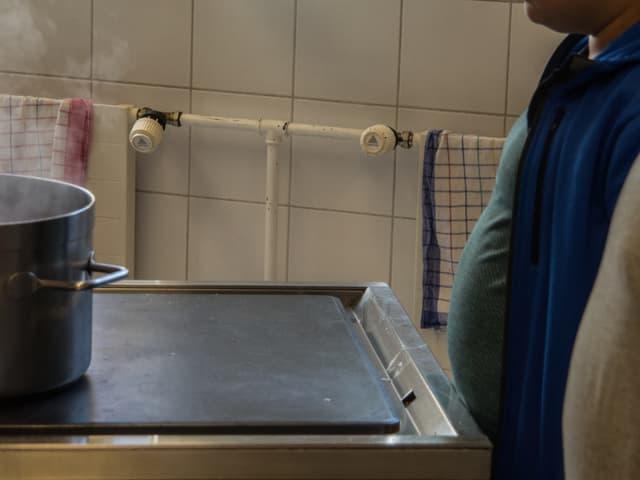 Zwei übergewichtige Jungen schauen auf einen Kochtopf.