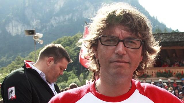 Ein Mann mit Brille vor Bergkulisse.